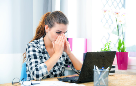 Stressed and thinking woman in home office using laptop